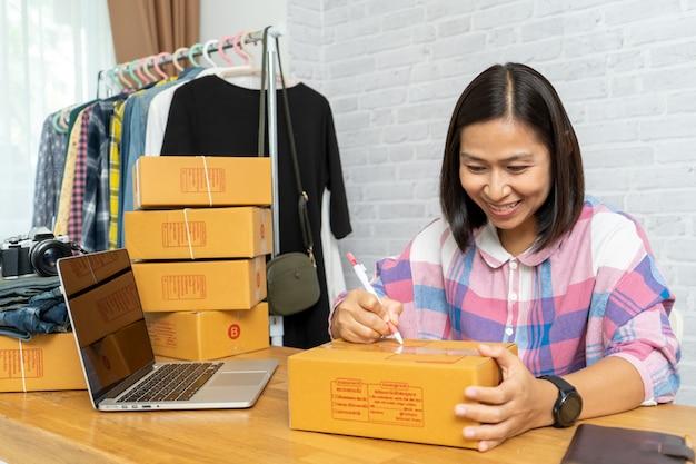 As mulheres asiáticas que vendem on-line iniciam o pequeno empresário trabalhando