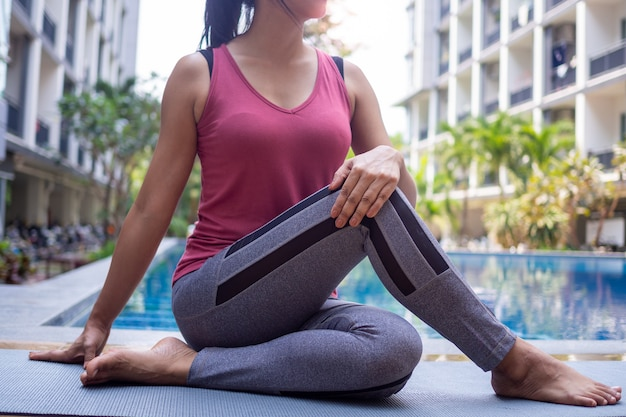 As mulheres asiáticas que vestem a roupa atlética, ioga, torcendo a pose, lado da piscina relaxaram conceitos saudáveis do exercício.
