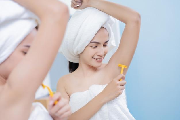 As mulheres asiáticas raspar suas axilas no banheiro