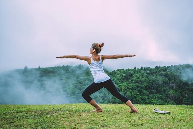 As mulheres asiáticas relaxam no feriado. jogue se yoga, florestas naturais, montanhas e neblina.