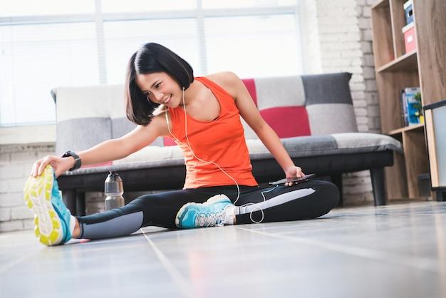 As mulheres asiáticas se aquecem antes do exercício em casa e ela está ouvindo.