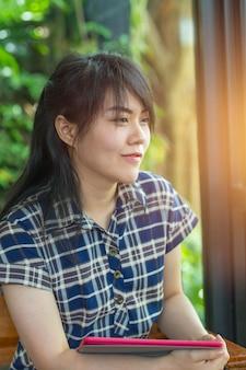 As mulheres asiáticas segurar tablet e sorrir pensando falta passou boa memória quando se olha para windows