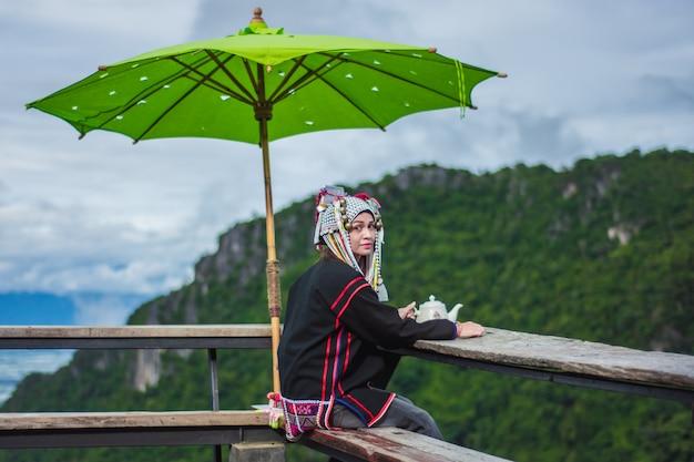 As mulheres asiáticas sentam-se no chá no topo da montanha.