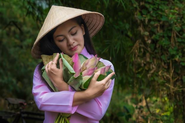 As mulheres asiáticas tradicionais vietnam são bicicleta do trole da menina à loja após a cesta da flor de lótus.