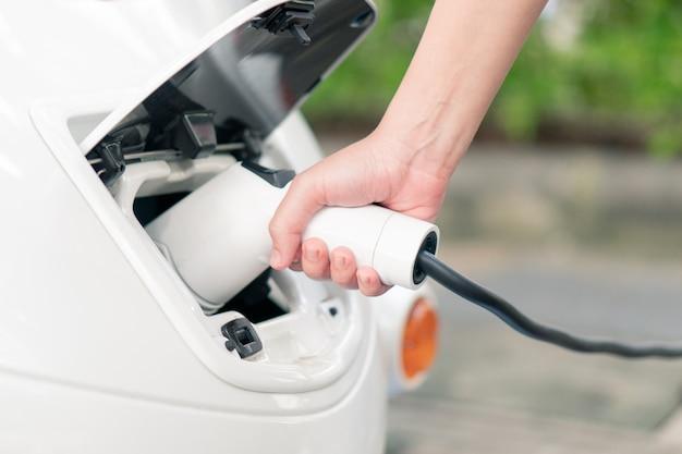 As mulheres asiáticas trazem carregadores de bateria conecte com o carro elétrico para põr o carro elétrico