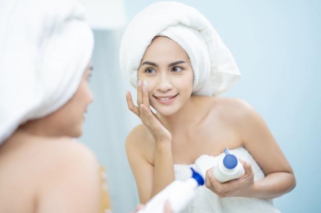 As mulheres asiáticas uma loção facial depois de um banho
