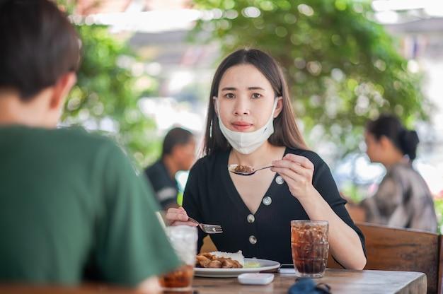 As mulheres asiáticas usam máscara facial sentado no restaurante foco suave, novo conceito normal