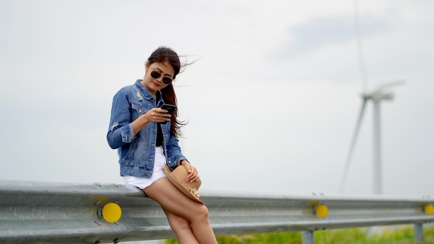 As mulheres asiáticas verificar telemóveis, pelo fundo como turbinas eólicas