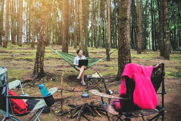 As mulheres asiáticas viajam natural relaxam o assento que senta-se usando um caderno.
