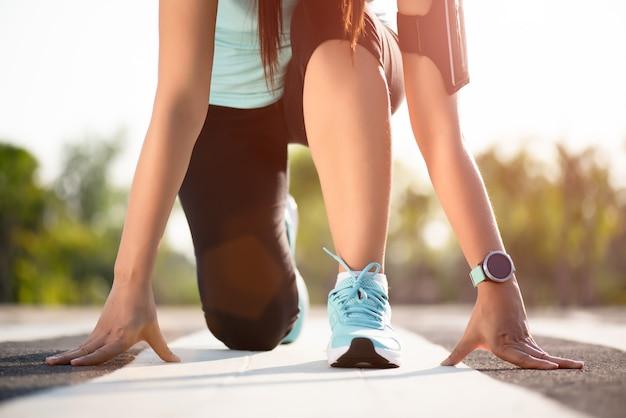 As mulheres atléticas no começo running levantam na pista de atletismo na rua do jardim.