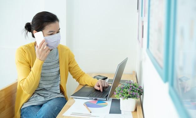 As mulheres bonitas asiáticas que usam máscaras trabalham em casa, usando notebook, tablet e smartphone, para reduzir a propagação do coronavírus. trabalhe em casa, distanciamento social e conceito de coronavírus.