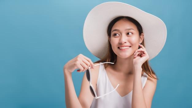 As mulheres bonitas de sorriso asiáticas blogueiras usam um chapéu largo e segurando óculos de sol isolados em fundo azul