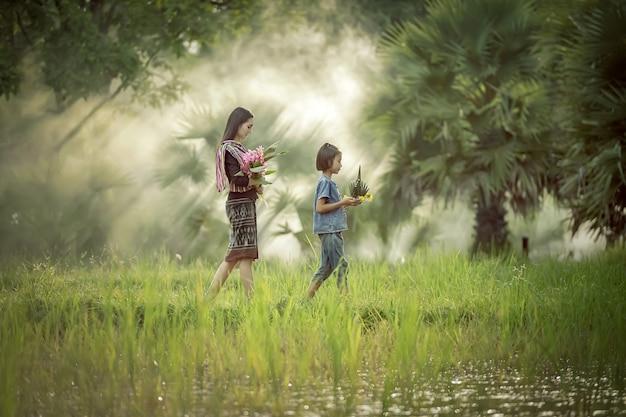 As mulheres camponesas asiáticas estão se preparando para adorar a deusa do arroz, regularmente, todos os anos da fazenda.