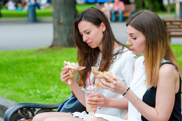 As mulheres caucasianos comem sanduíche de fast-food de hambúrguer na rua ao ar livre. meninas ativas com fome e comendo comida de rua depois de uma longa caminhada