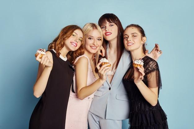 As mulheres celebram festa de férias se divertindo comem bolos
