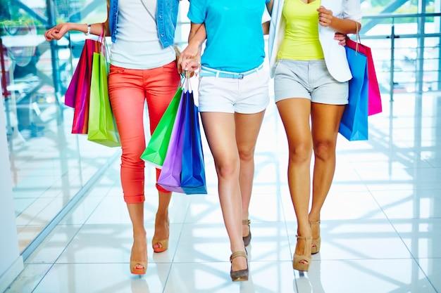 As mulheres com saltos altos e sacos de compras