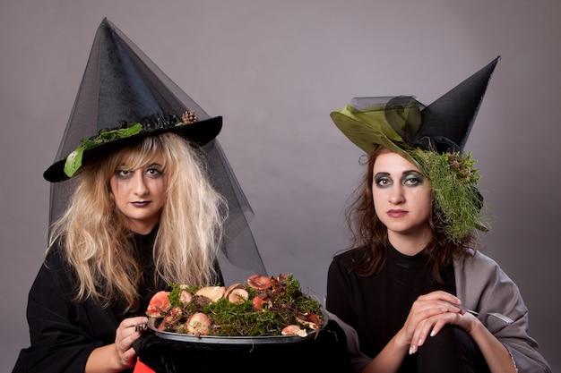 As mulheres compõem como bruxas para o halloween