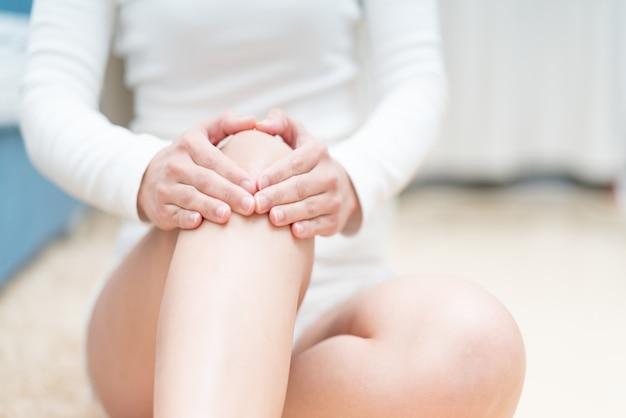 As mulheres da dor do joelho que sentam e tocam em seu joelho, cuidados médicos e conceito da medicina