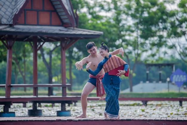 As mulheres da tailândia e o homem em traje nacional dança tailandesa