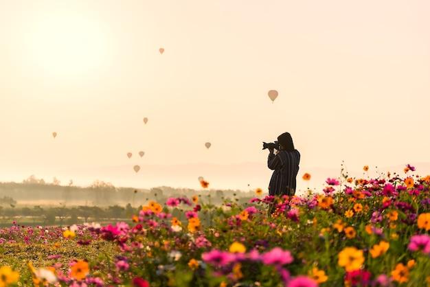 As mulheres de ásia fotografaram a flor e o balão, silhueta do fotógrafo que toma a imagem da paisagem d