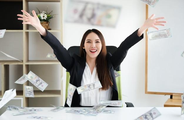 As mulheres de negócio abraçam o dinheiro no escritório ela, conceito para o negócio do sucesso e liberdade financeira.