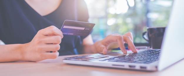 As mulheres de negócios mão usam cartões de crédito e computadores portáteis para fazer compras on-line.