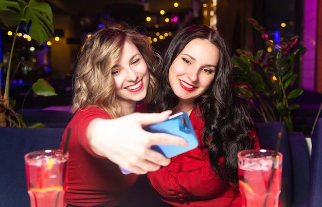 As mulheres de vestidos vermelhos bebem coquetéis e comemoram em uma boate ou bar.