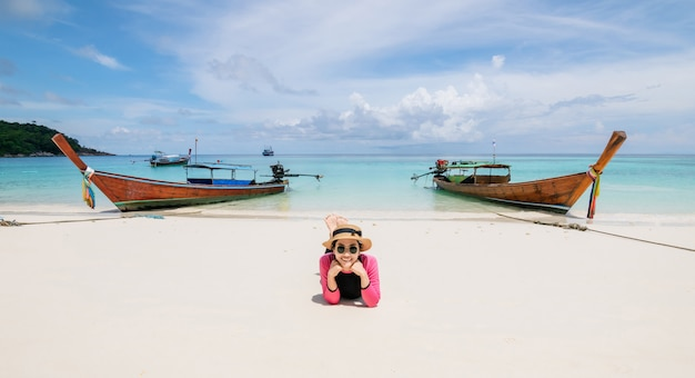 As mulheres deitar na praia e no mar tem um verão de férias relaxantes