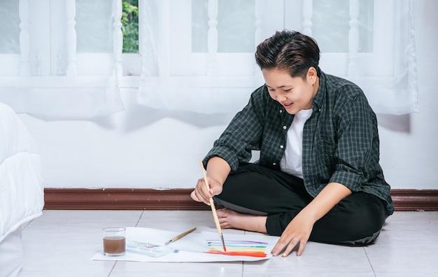 As mulheres desenham e pintam água no papel.
