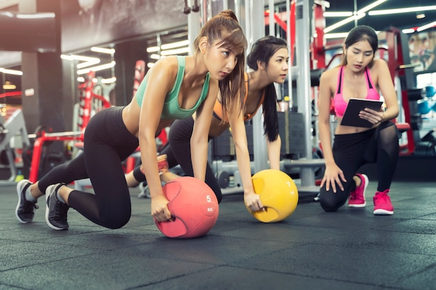 As mulheres do esporte exercitam juntos no ginásio com treinador