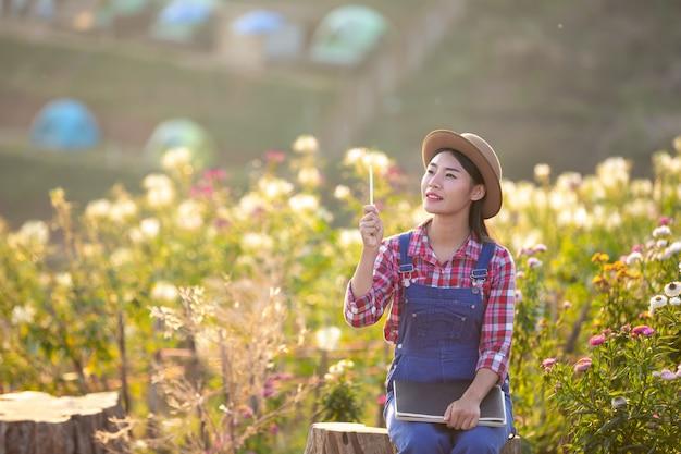 As mulheres dos fazendeiros estão tomando notas no jardim de flor.