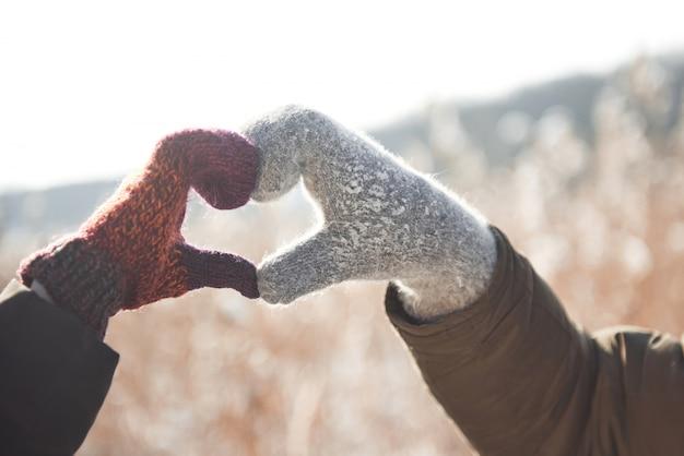 As mulheres e as mãos do homem na luva dobrada em forma de coração. conceito de inverno. queda de neve.