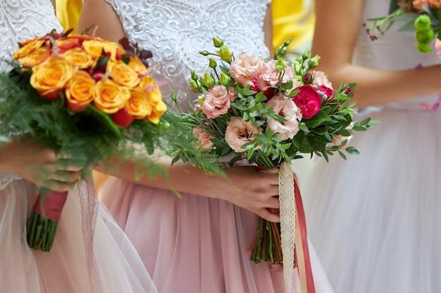 As mulheres em vestidos brancos estão segurando lindos buquês de casamento nas mãos