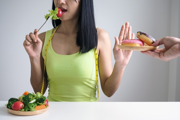 As mulheres empurram pratos que se pensa serem uma mistura de gordura trans. perder peso, não comer farinha