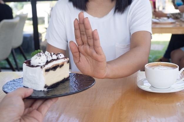 As mulheres empurravam o prato do bolo com as pessoas. não coma sobremesas para perder peso.