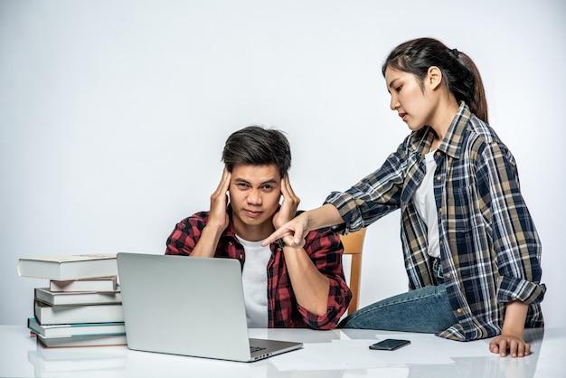 As mulheres ensinam os homens a trabalhar com laptops no trabalho.