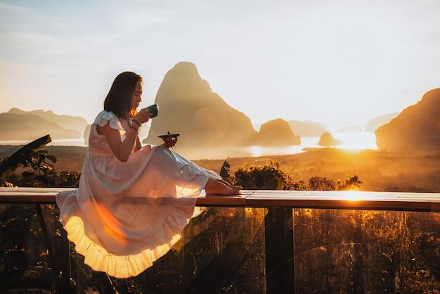 As mulheres estão bebendo o café no ponto de vista da ilha de sametnangshe, phang nga, tailândia.