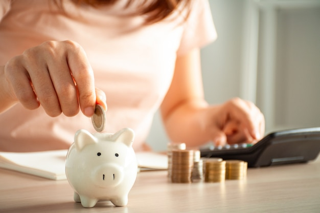 As mulheres estão colocando moedas em um cofrinho para um negócio que cresce com lucro e economiza dinheiro para o futuro. planejamento para o conceito de aposentadoria