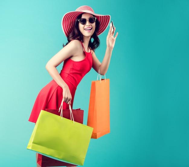As mulheres estão comprando no verão, ela está usando um cartão de crédito e gosta de fazer compras.