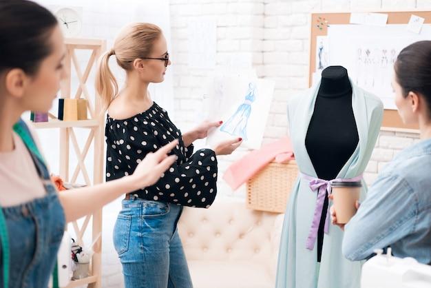 As mulheres estão discutindo design e cor para novo vestido.