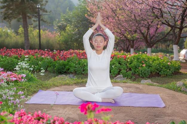 As mulheres estão jogando yoga no parque