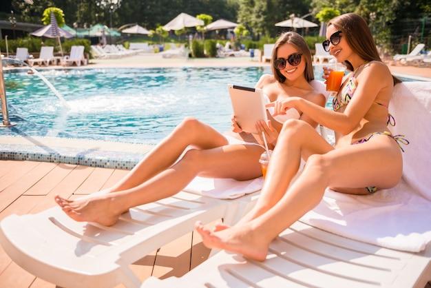 As mulheres estão mentindo sobre chaise-longue e usando tablet digital.