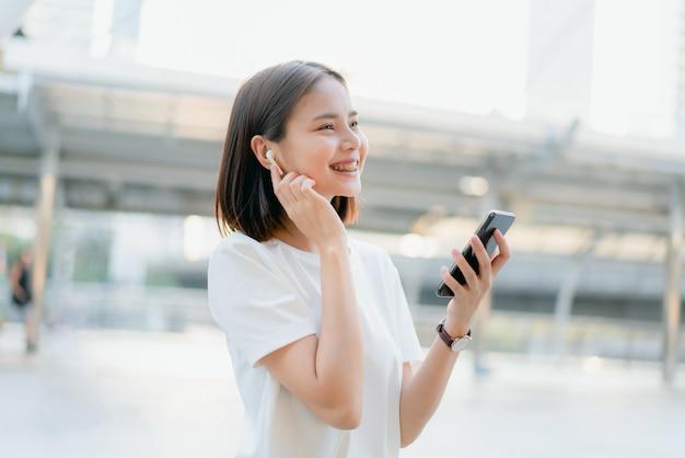 As mulheres estão ouvindo música de fones de ouvido brancos. e usando as mãos toque para usar várias funções, humor feliz.