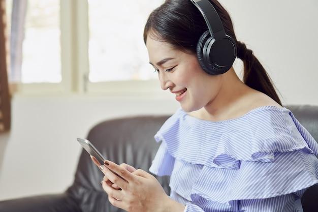 As mulheres estão ouvindo música de fones de ouvido pretos. de bom humor e conforto.
