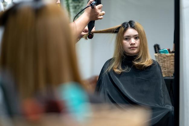 As mulheres estão soprando cabelo no salão de cabeleireiro.