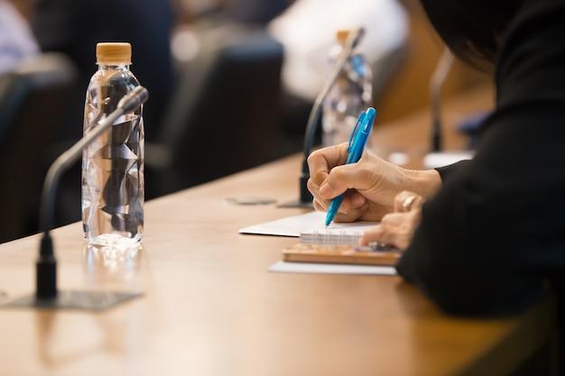As mulheres estão tomando notas na sala de reuniões.
