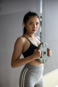 As mulheres exercitam com halteres no peito.