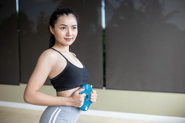 As mulheres exercitam com placas de peso com halteres no abdômen.