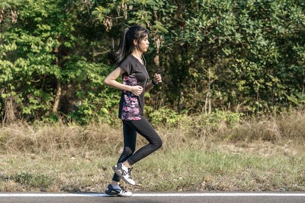 As mulheres exercitam correndo na estrada.