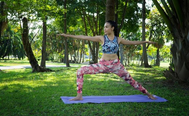 As mulheres fazem yoga no parque